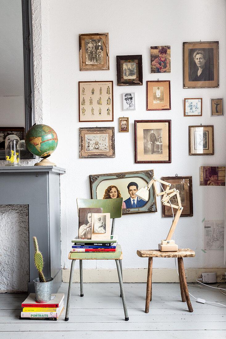 Nostalgische Bilder in Sepia an der Wand über altem Stuhl und Hocker