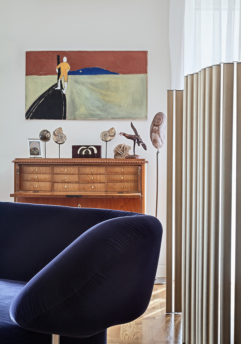 Designer sofa in front of screen made from cardboard tube and antique bureau in open-plan interior