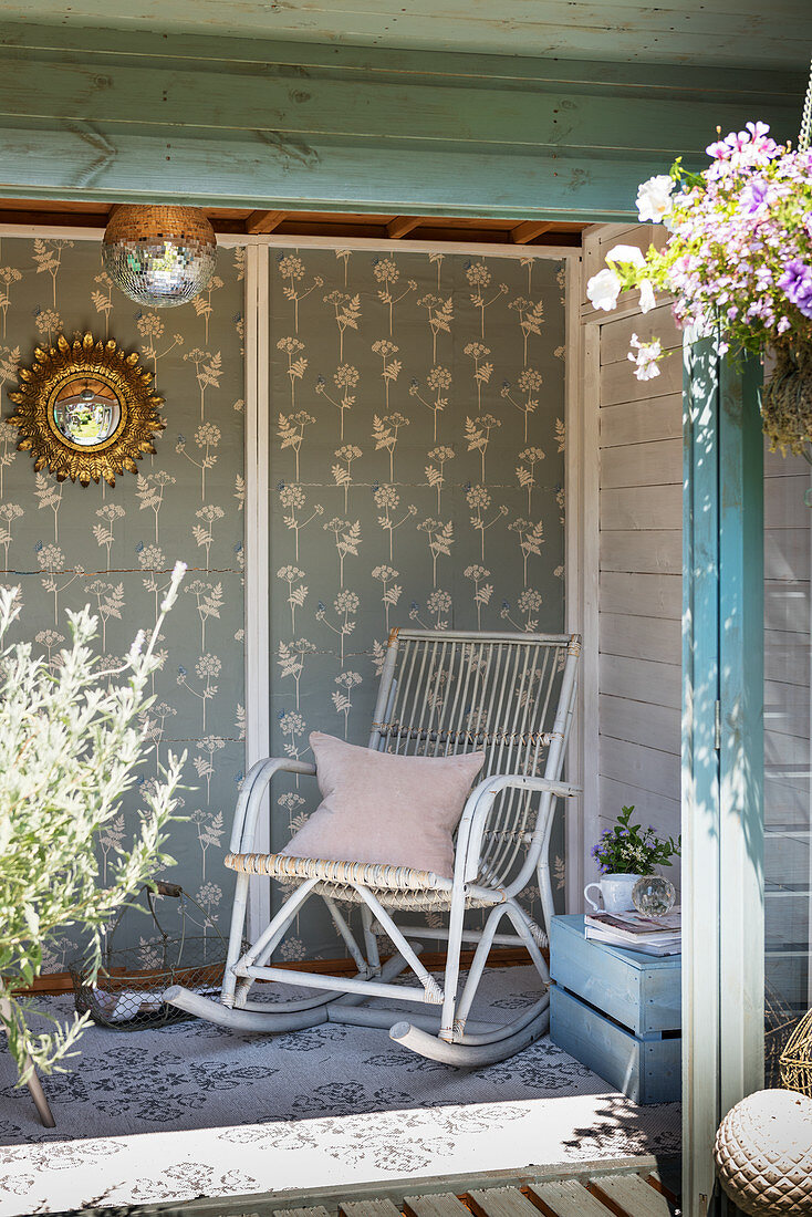 Old wooden rocking chair in summerhouse with patterned wallpaper on back wall