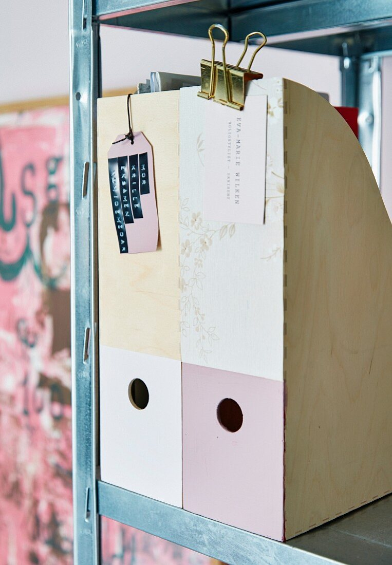 Decoupaged and painted magazine files on metal shelves