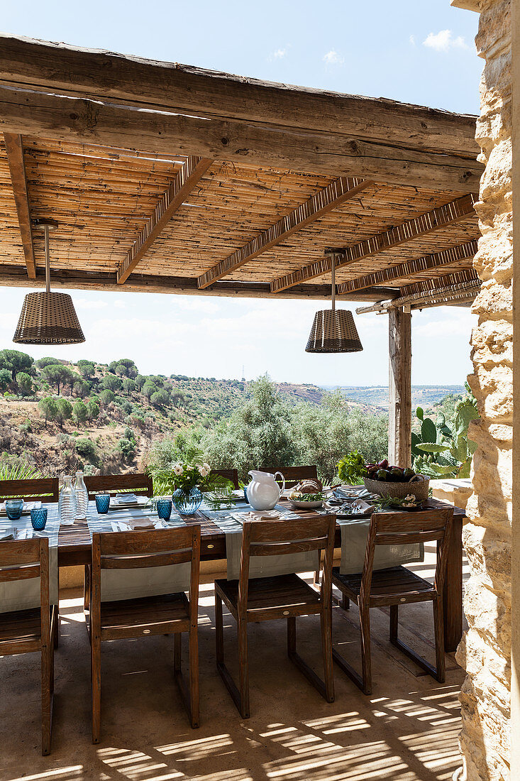 Set dining table and chairs on roofed terrace