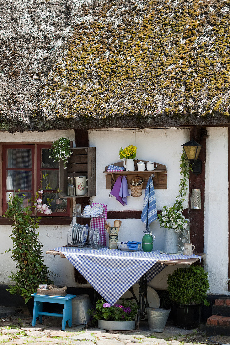 Vintage outdoor kitchen on exterior wall of old half-timbered house with thatched roof