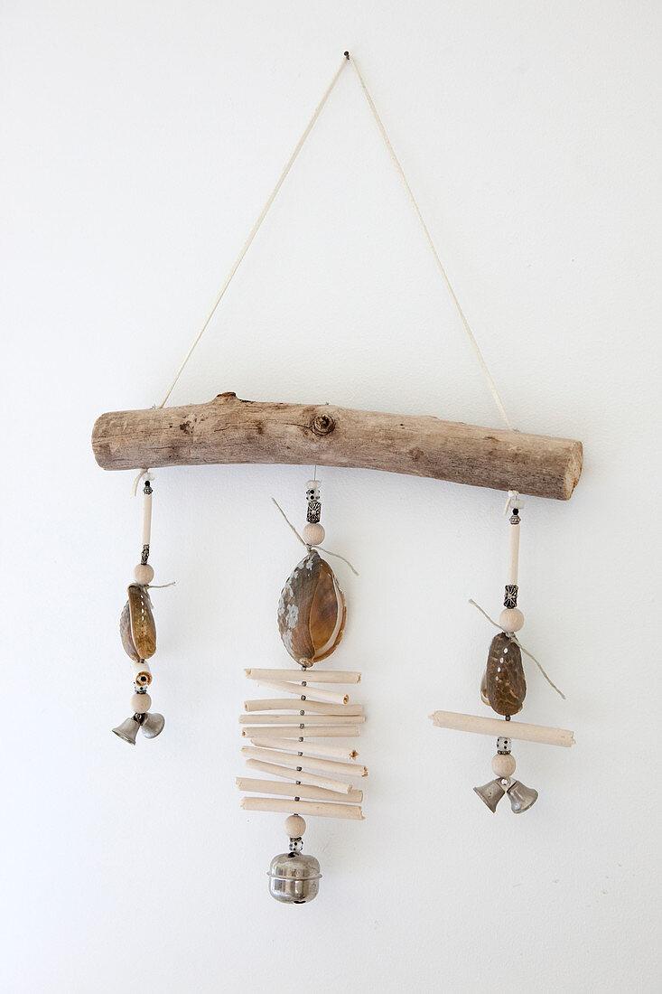 Mobil made from shells, wood and little bells hung on white wall