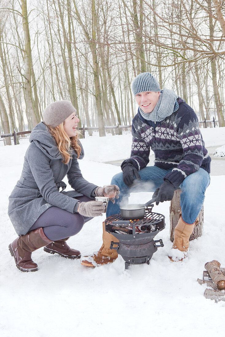 Couple cooking brazier in snowy landscape
