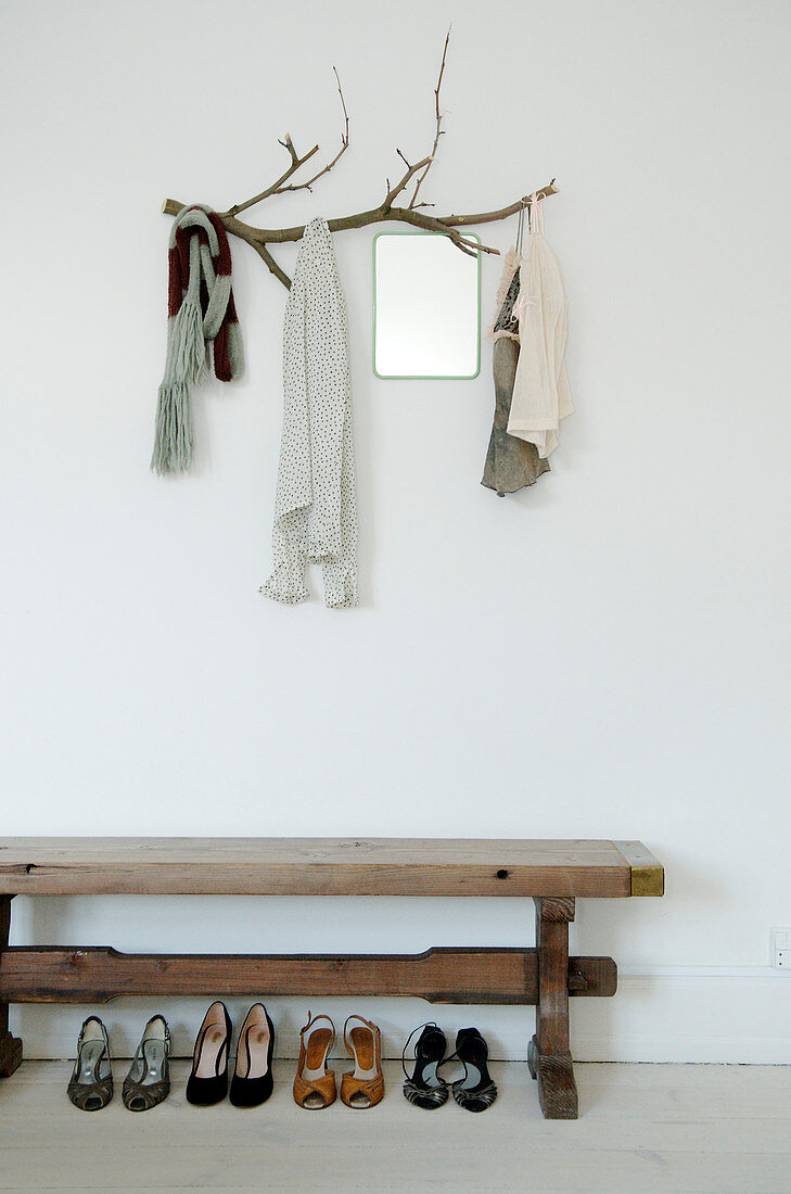Shoes under a wooden bench and branch as a cloakroom in the hallway