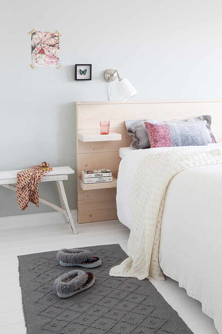 Double bed with wooden headboard in bright bedroom