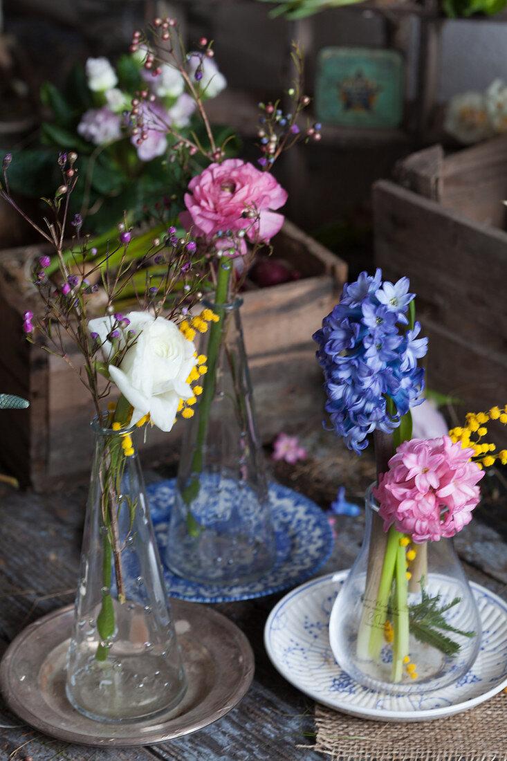 Ranunculus, hyacinths, Australian waxflowers and mimosa flowers in glass vases