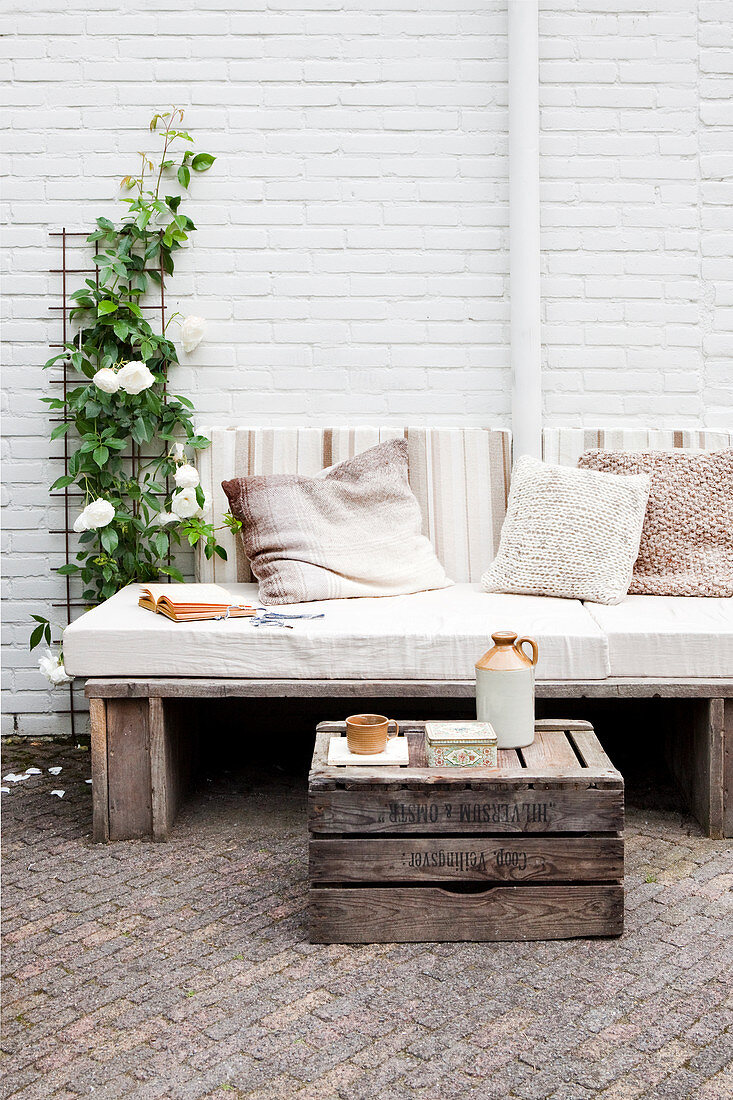 Rustic bench with seat cushion and scatter cushions against white-painted brick wall with old wooden crate used as table