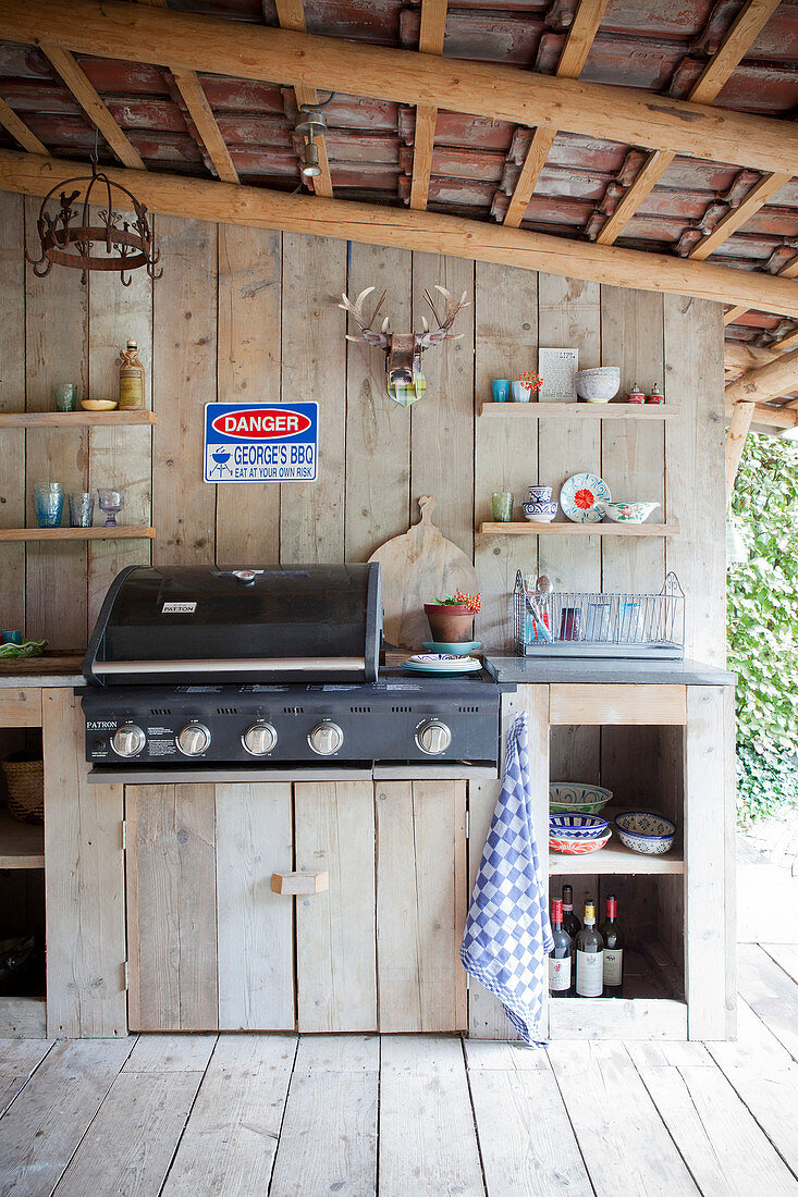 Outdoor kitchen on a covered terrace with a wooden wall