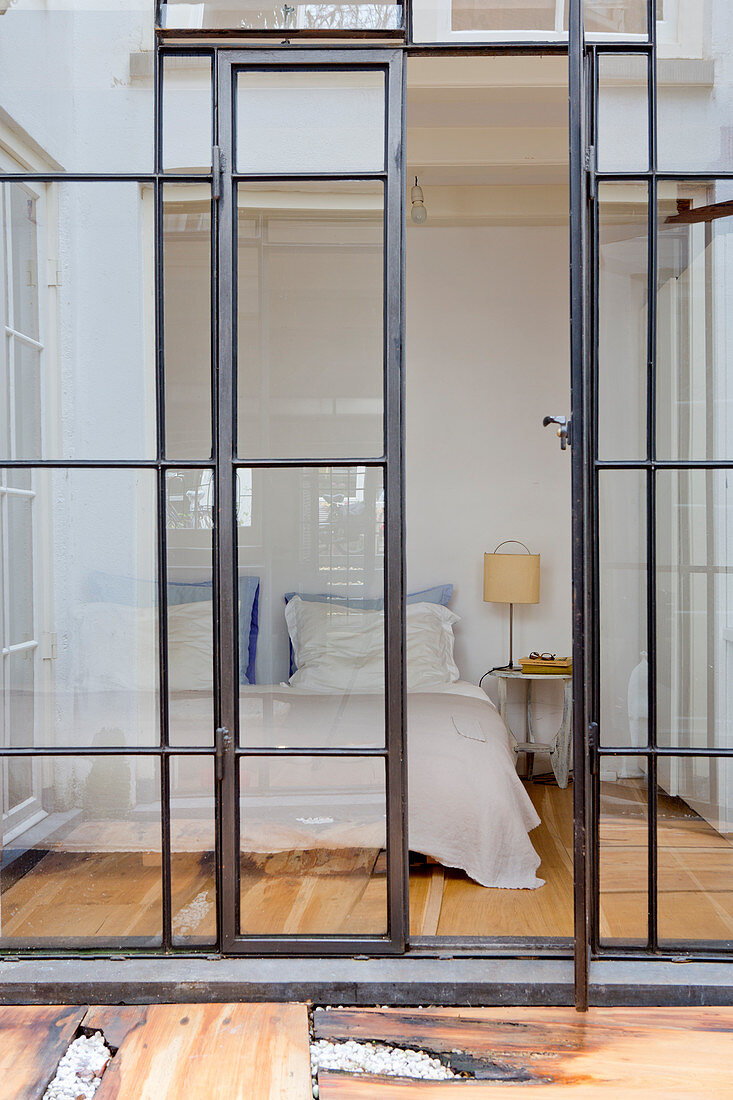 Double bed in bedroom seen through industrial-style glass wall and doors
