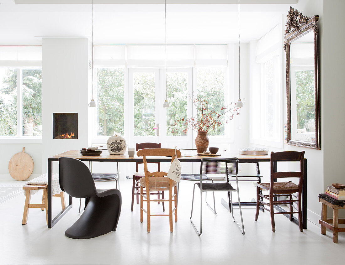Long dining table with various chairs in bright dining area