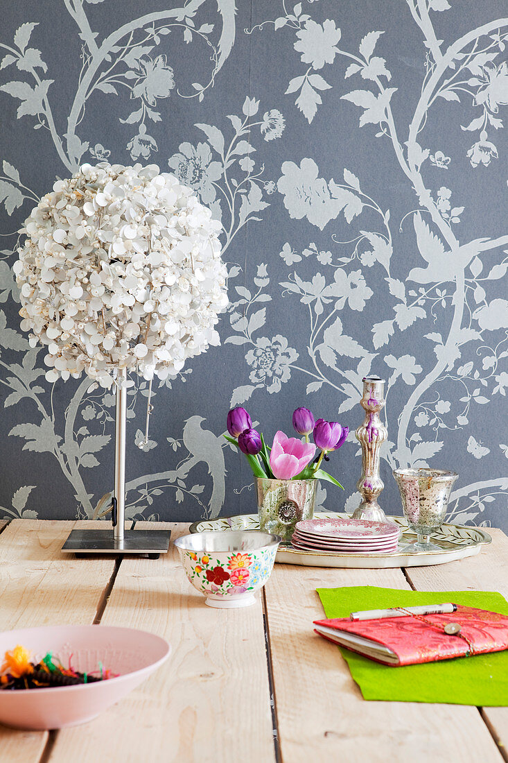 Table lamp, tulips, candle holder, and bowl on wooden table in front of wallpaper with floral pattern