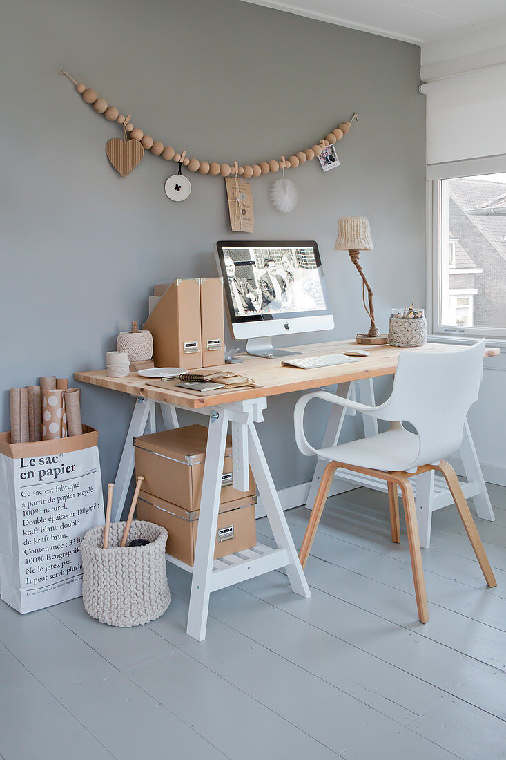 Desk and white chair below wall hanging made from wooden beads on grey wall of study