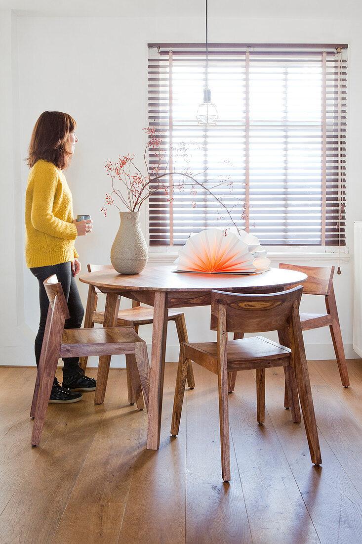 Frau am Fenster im schlichten Esszimmer mit Holzmöbeln