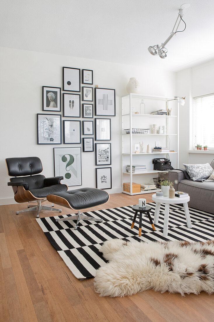 Classic Eames Lounge Chair, gallery of pictures and shelves in room decorated in black and white