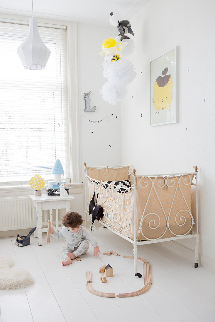 Child playing on floor next to vintage bed in bright bedroom