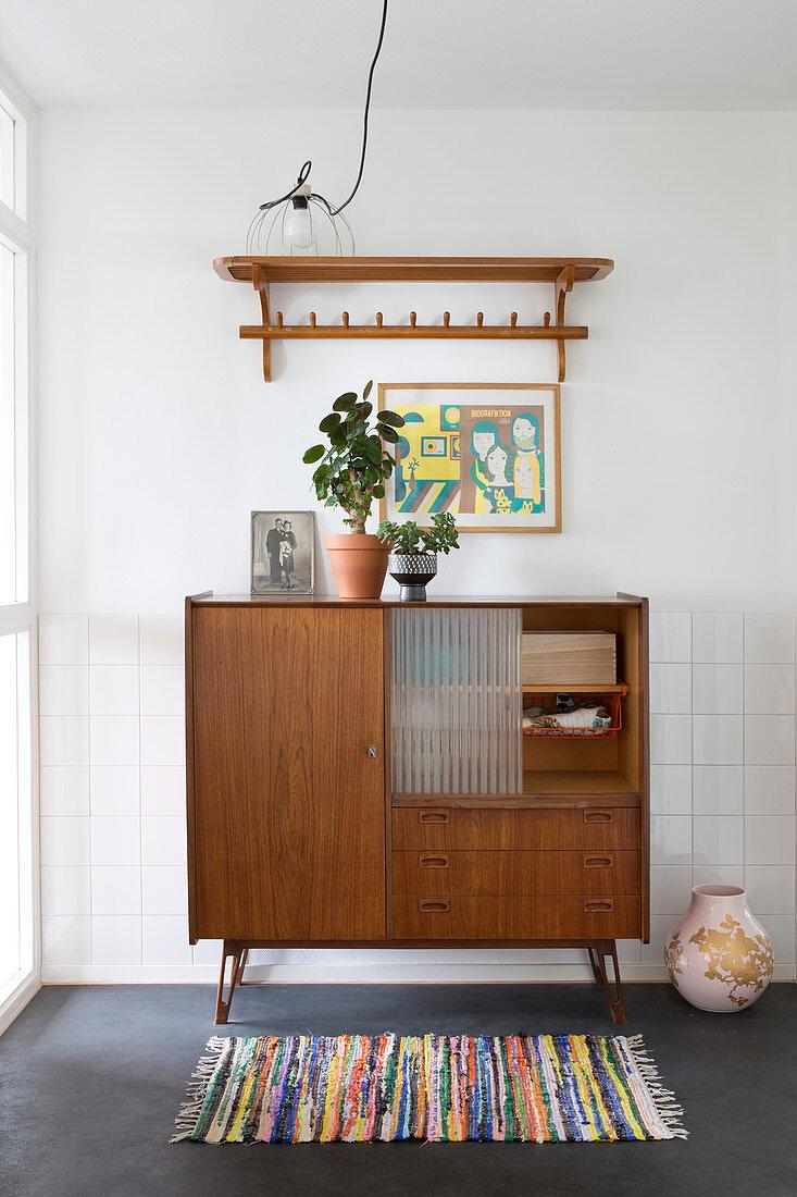 Houseplants on retro sideboard below lampshade resting on shelf
