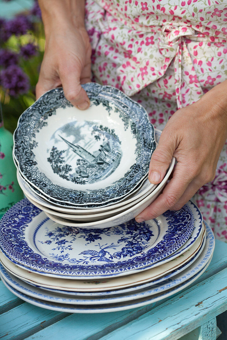 Hands holding stack of old plates and bowls with classic pattern
