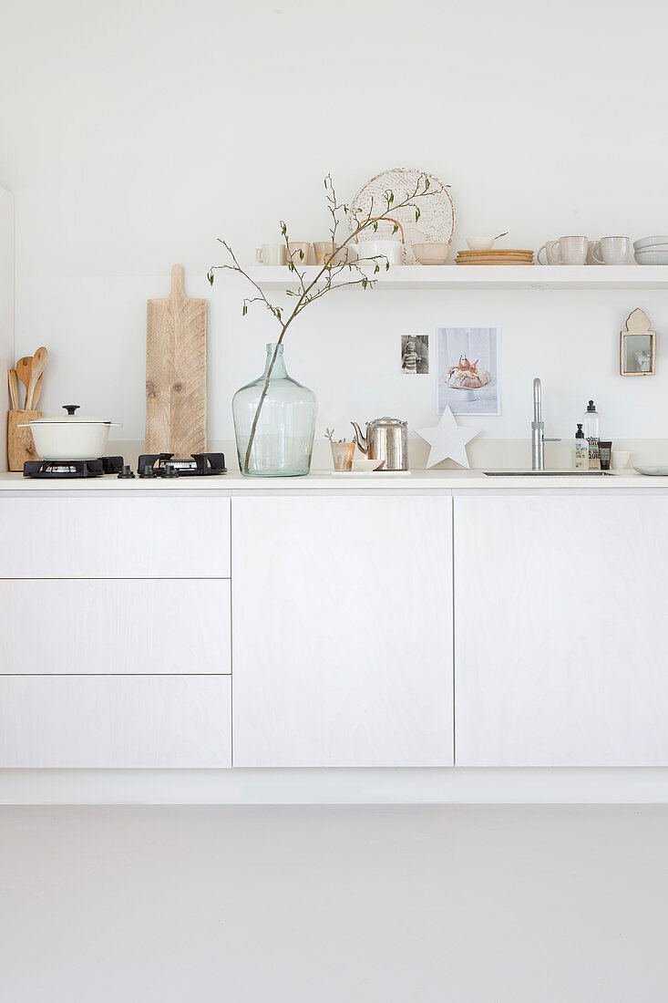 Gas hob and branch in demijohn on white kitchen counter