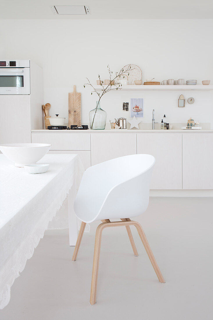 White shell chair at table with white tablecloth in kitchen-dining room with white kitchen counter