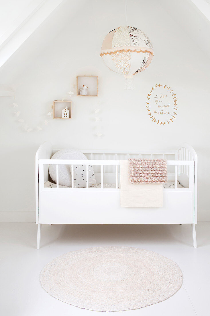 White cot below accessories on wall in attic room