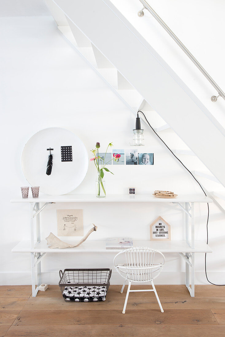 Ornaments on white console table below stairs