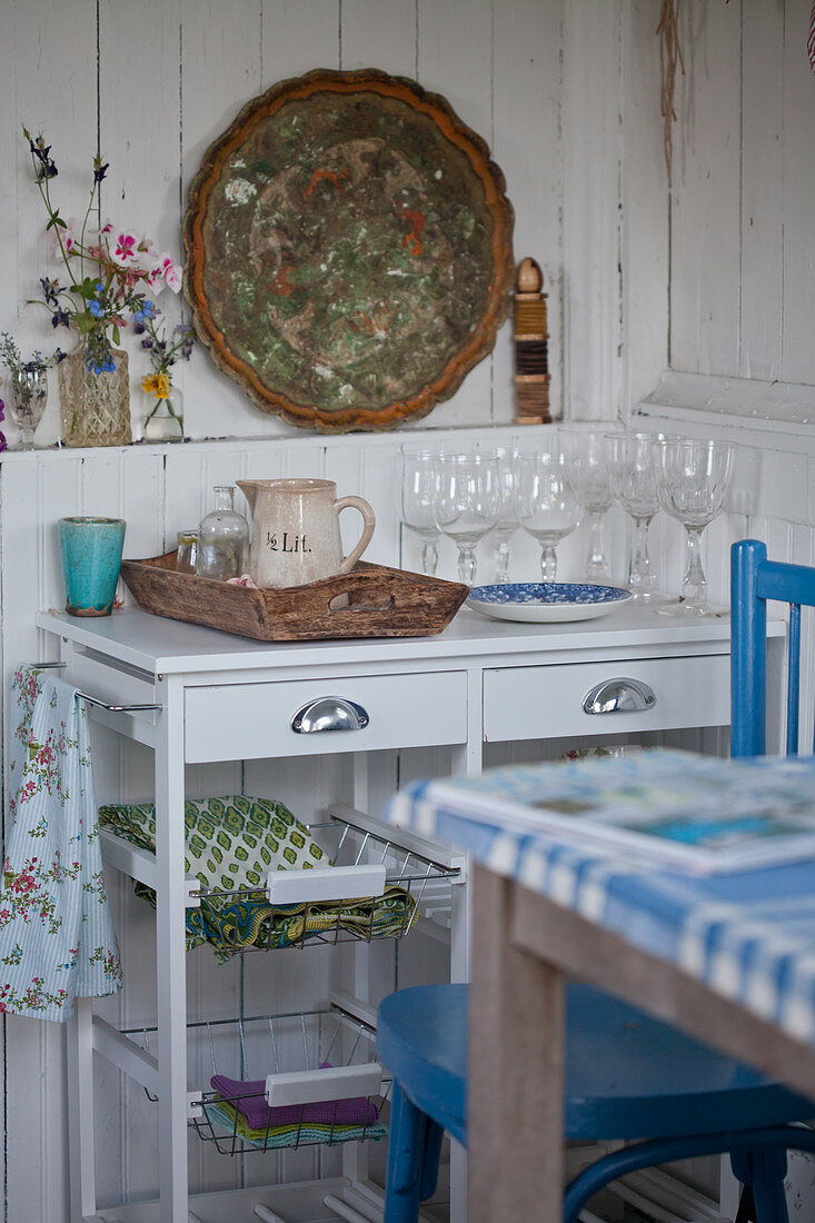 Drinking glasses on serving trolley against rustic, white board wall