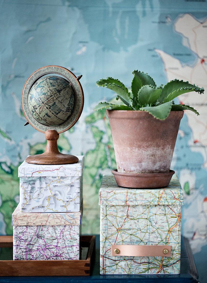 Globus und Brutblatt auf mit Landkarten beklebten Schachteln