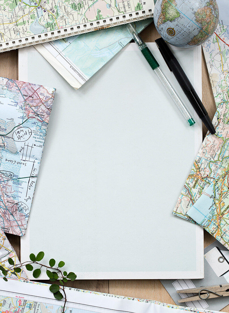 Blank sheet of paper, pens, and maps for travel planning