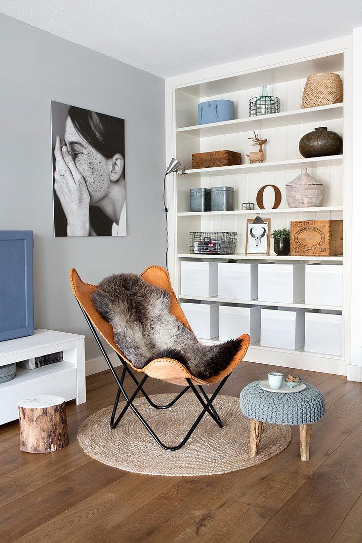 Designerstuhl aus Leder auf rundem Teppich vor dem Regal