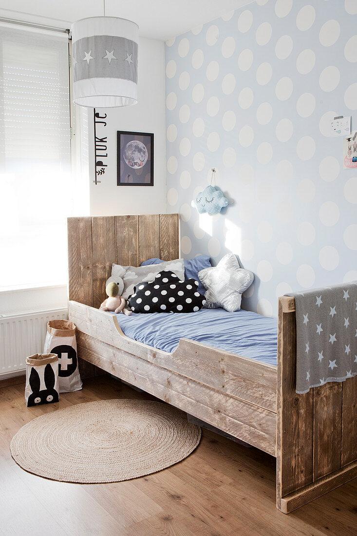 Kinderbett aus Altholz vor gepunkteter Tapete