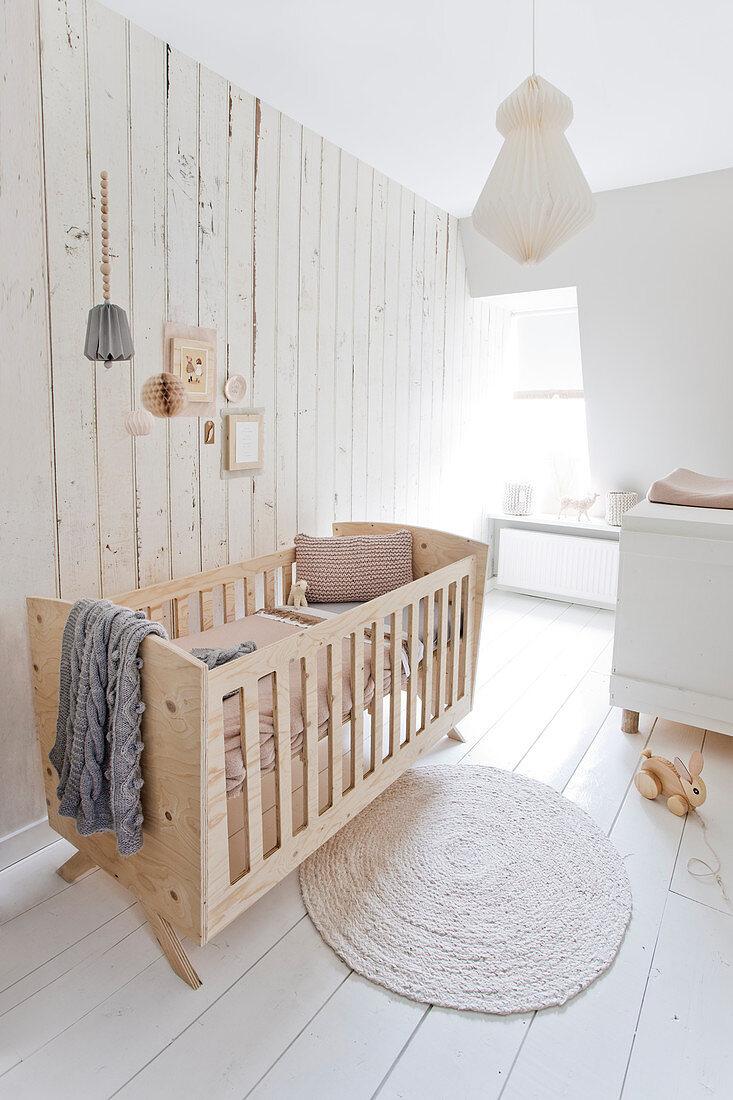 Gitterbett vor der Bretterwand im Kinderzimmer ganz in Weiß