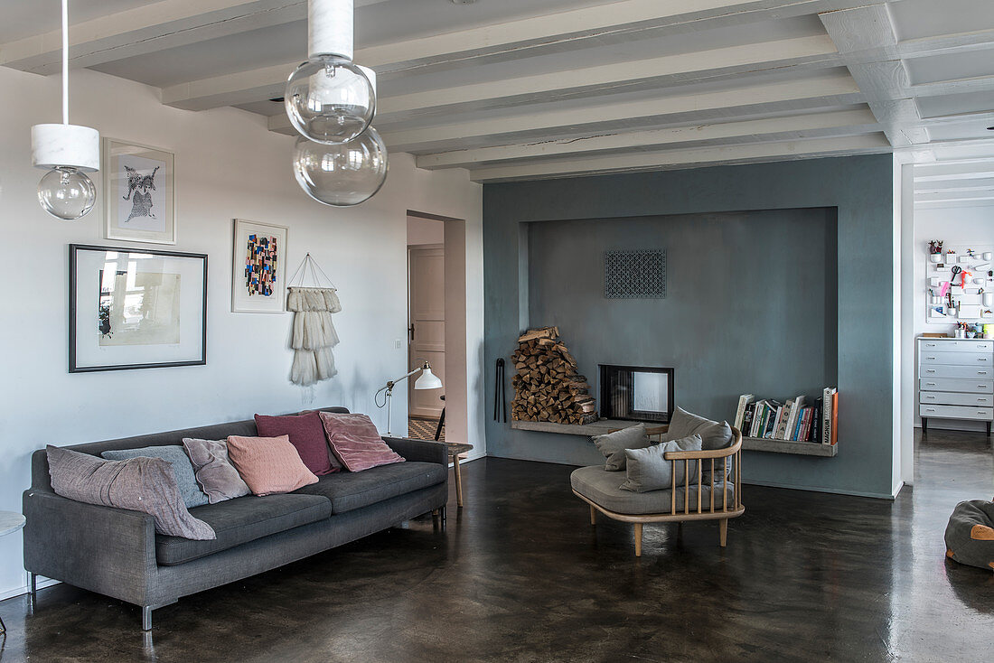 Cosy chair and sofa on concrete floor in front of fireplace with blue wall