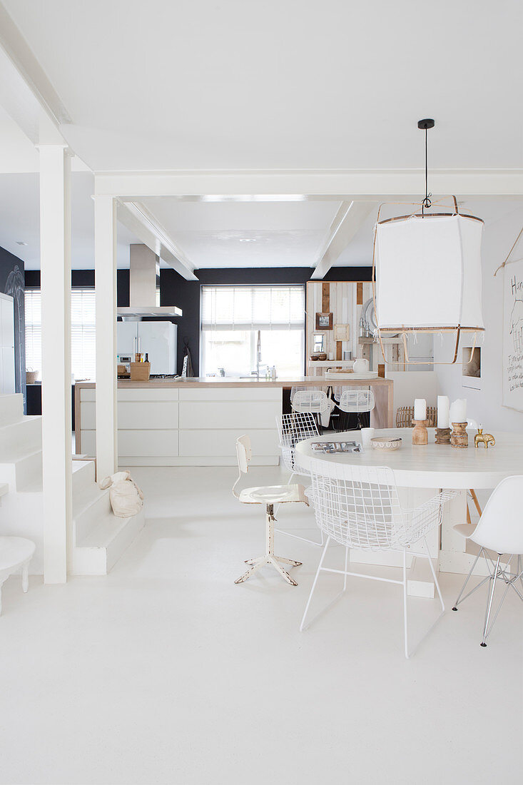 Round table with various chairs in front of the kitchen island and stairs in a white, open living room