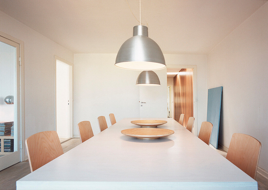 Two industrial lights above the dining table with modern chairs