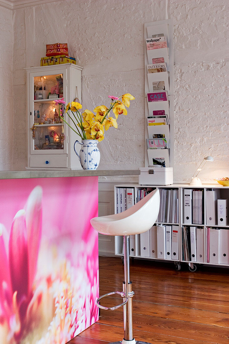 Magazine holder and display case on the wall above a shelf with folders