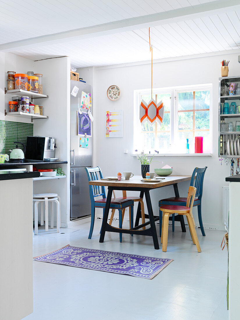 Various chairs at a dining table in kitchen living room with white floor