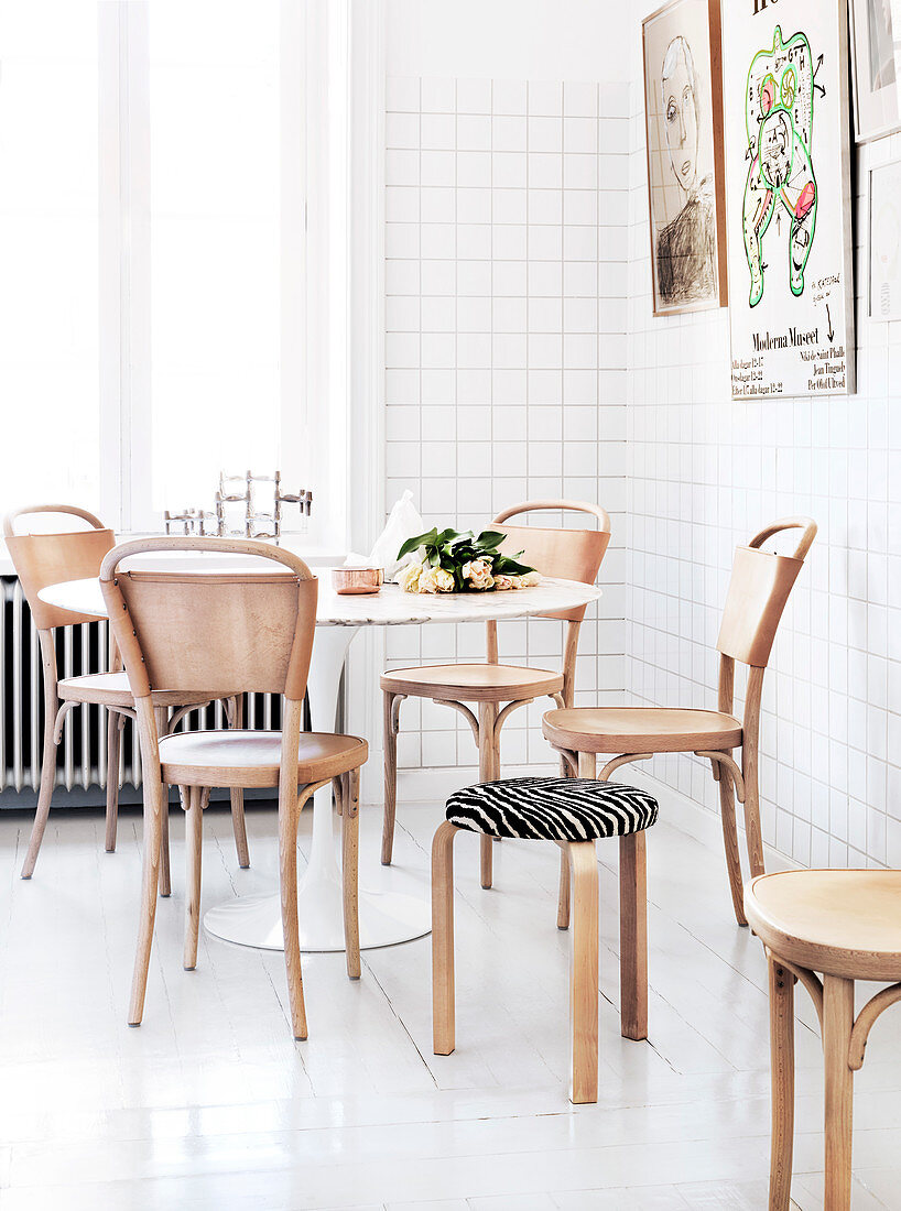 Light wood chairs with leatherbacks on the round table