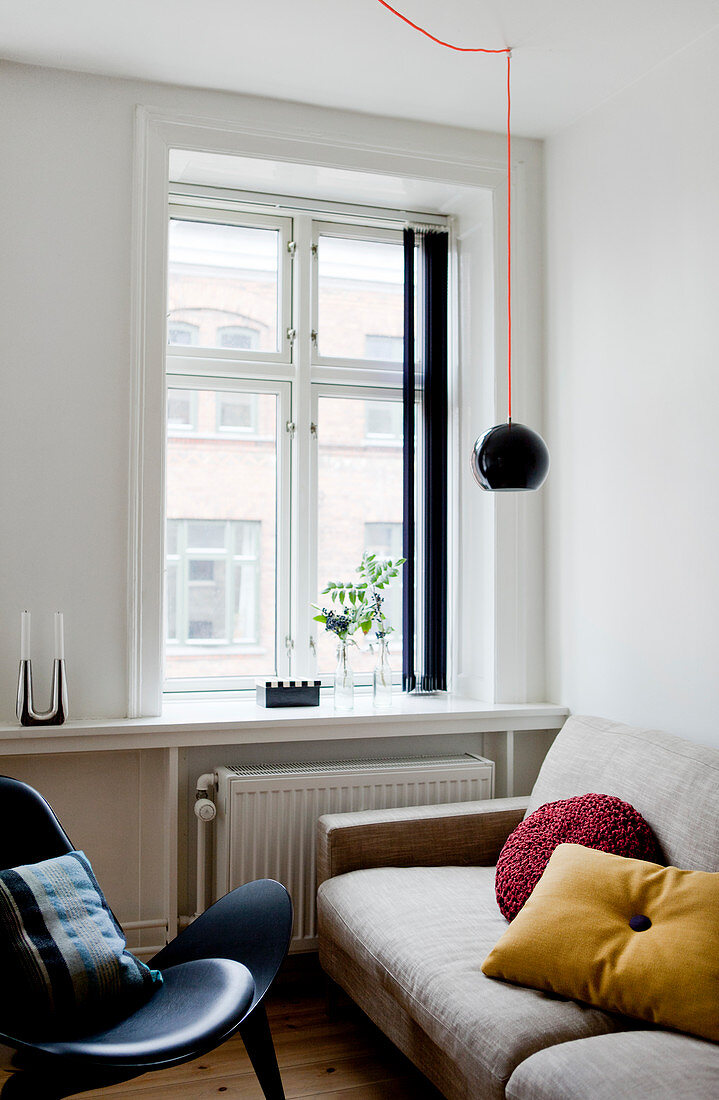 Light couch and black designer chair in front of the window in a living room