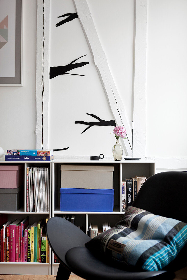 Black chair with cushions in front of a shelf with books, above a stylized branch as a wall decoration