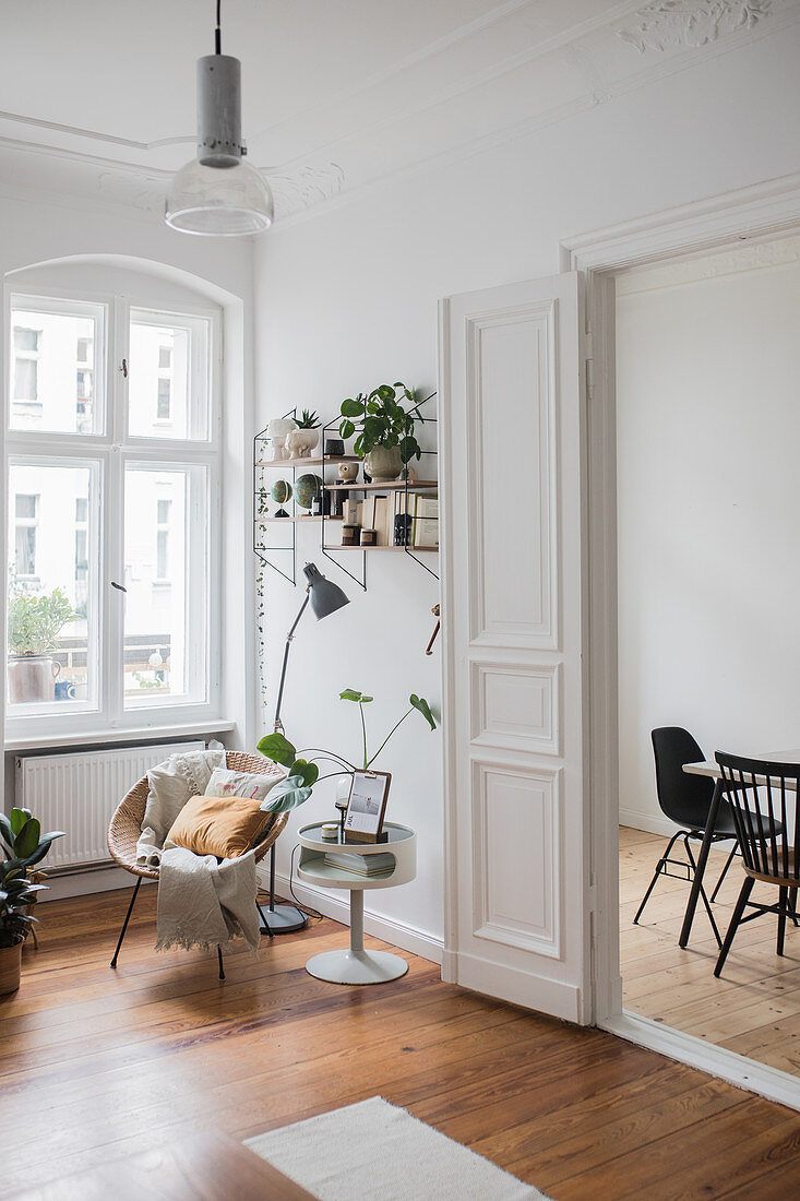 Seating area in living room of period apartment with panelled doors