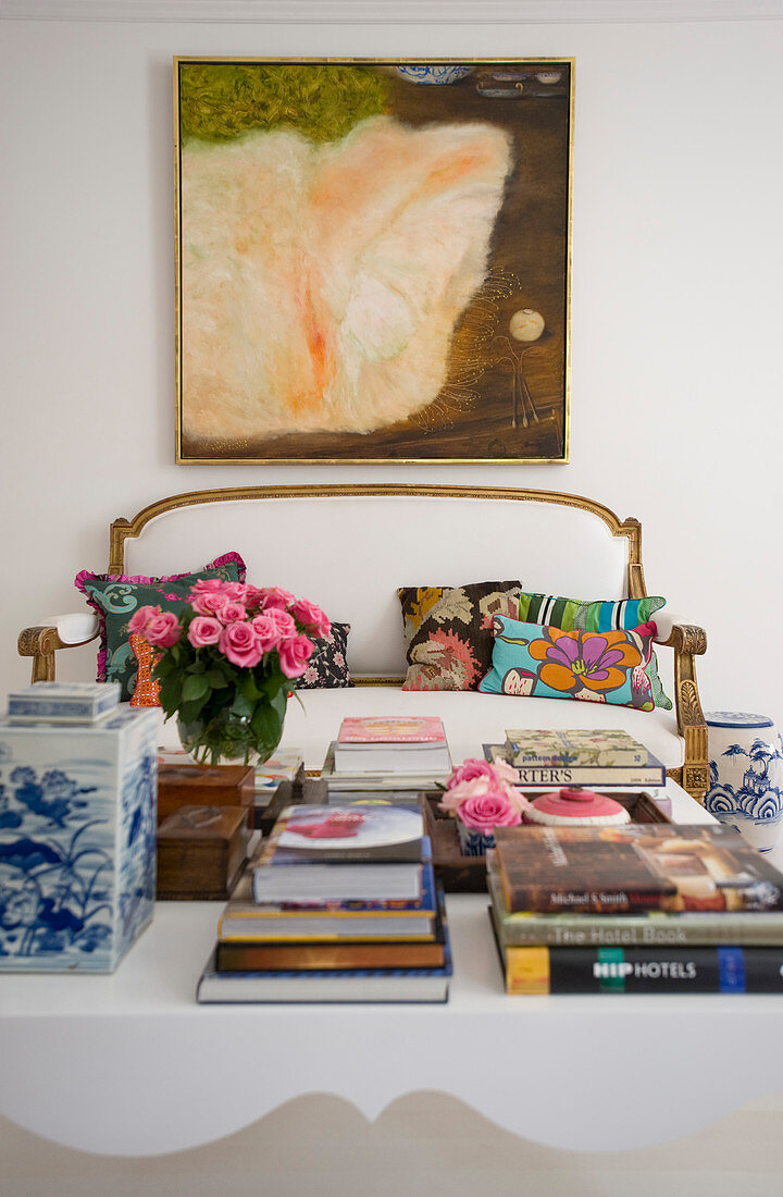 View past books on coffee table to antique sofa with white cover below painting
