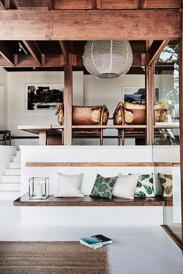 Two-part lounge in the split-level house: built-in bench with cushions below, vintage leather armchair above