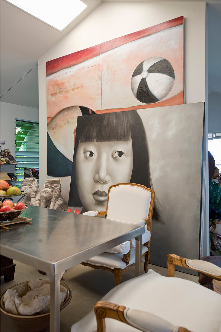 Large artworks behind metal table and Baroque chairs