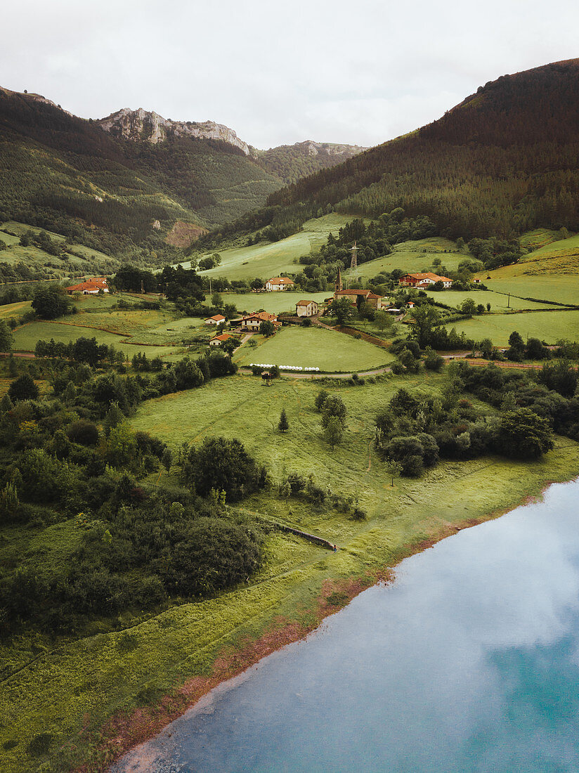Green fields and scattered houses between mountains and waters