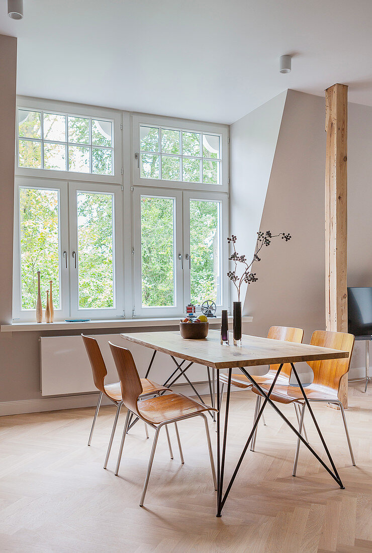 Dining area in front of window in open-plan interior