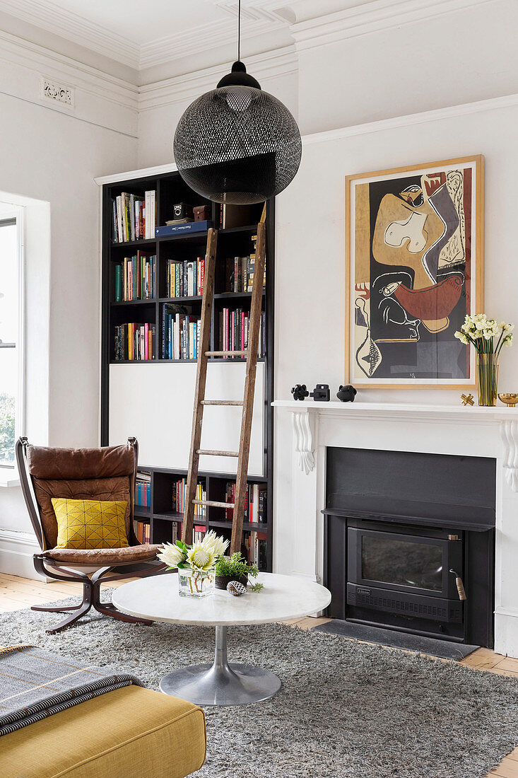 Coffee table and classic chair in front of fireplace and bookcase with ladder in living room