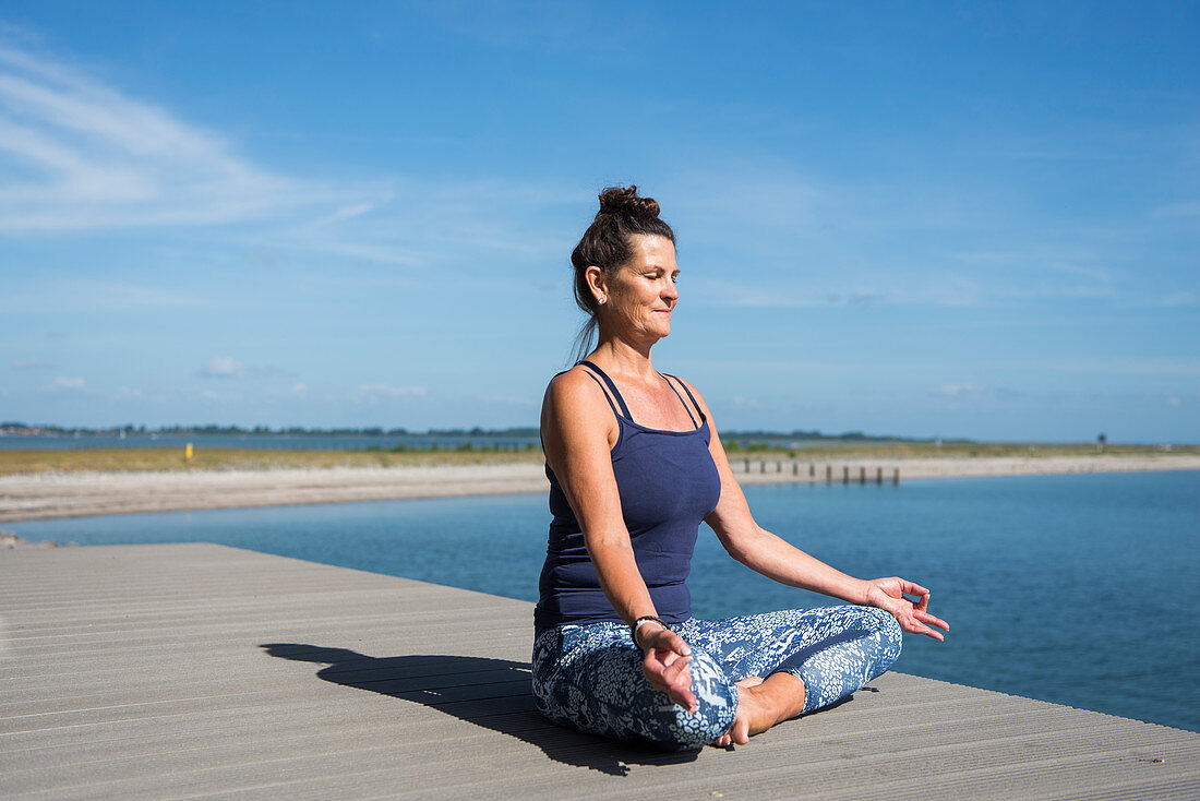 Woman sitting in the lotus position next to the sea