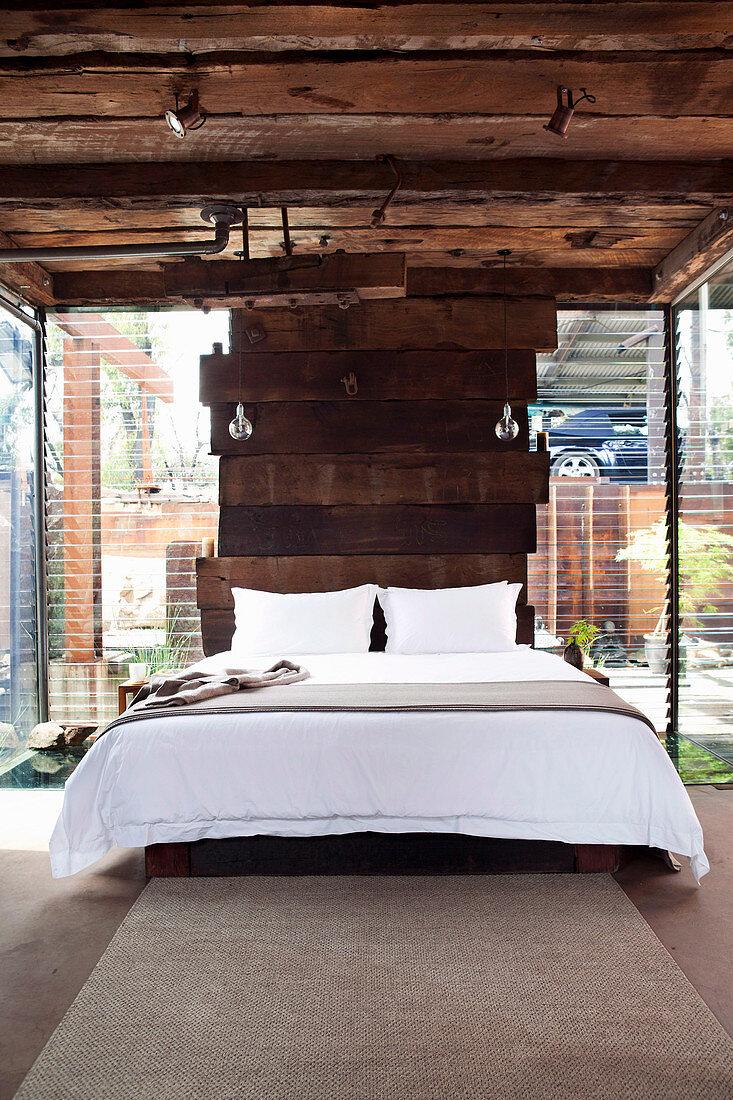 Bett vor Wand aus Holzbohlen im Schlafzimmer mit Lamellenfenstern