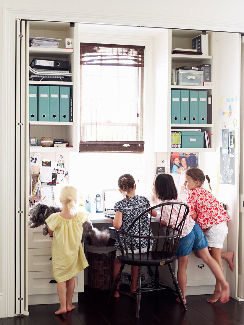 Four girls at the desk behind an open accordion door